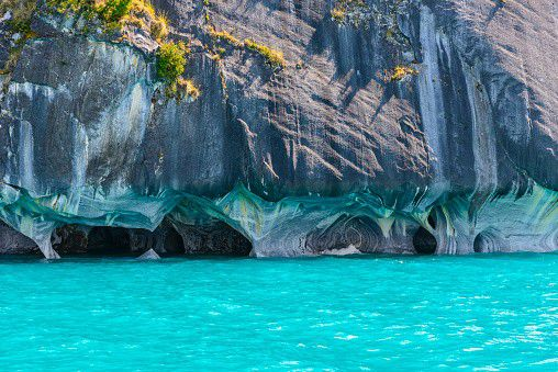 The Marble Caves are caves in Chile. They are located on the edge of a lake in the rugged landscape of Patagonia. Deep in the Andes mountains lies the glacial General Carrera Lake. It is shared by Chile and Argentina. In the Chilean part are the Cuevas de Mármol, or The Marble Caves. It is a place that has become known through social media, and is one of the most photogenic places in America